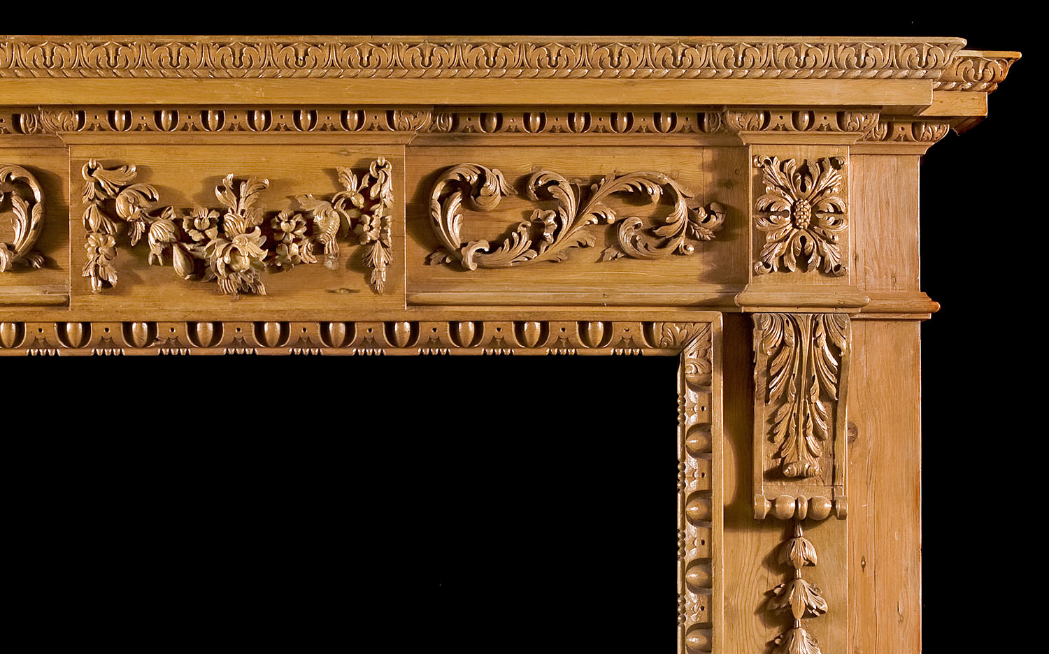 An ornately carved antique pine Neo Classical style fireplace surround
