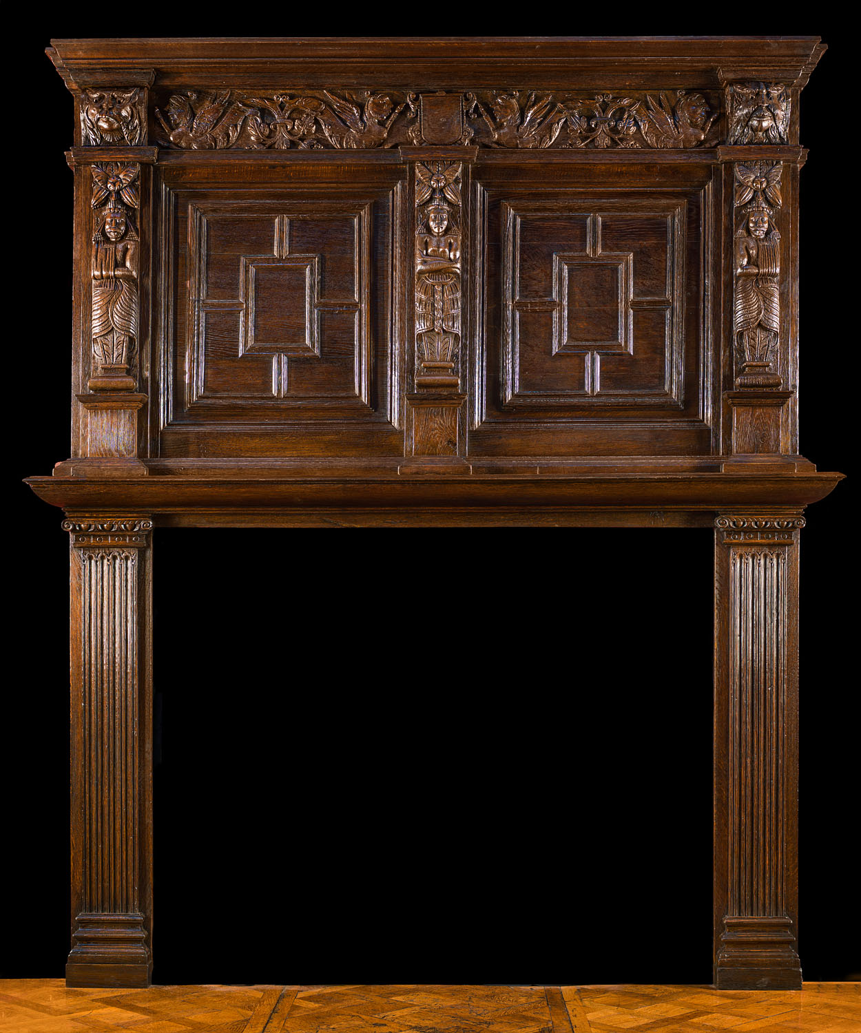 A large antique Jacobean style oak fireplace surround & overmantel