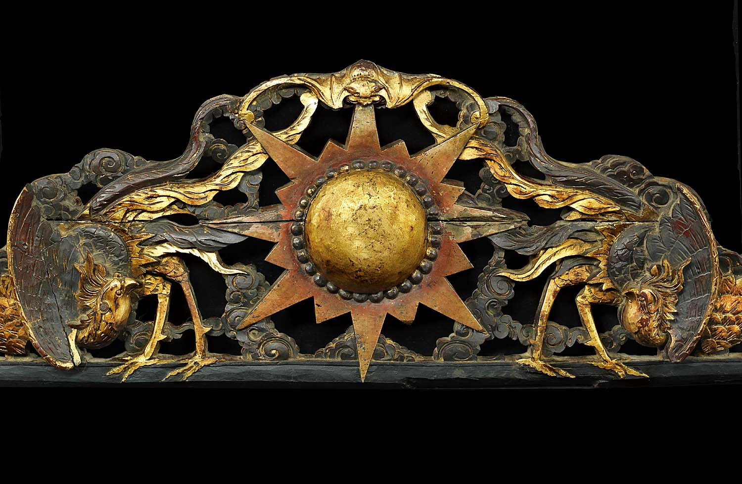 An antique carved wood pediment the phoenix and sun symbolising renewal