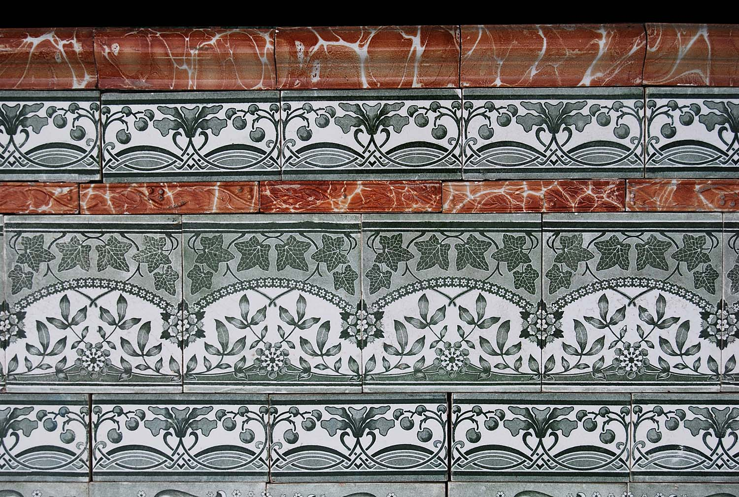 A suite of antique green and white Victorian floral tiles