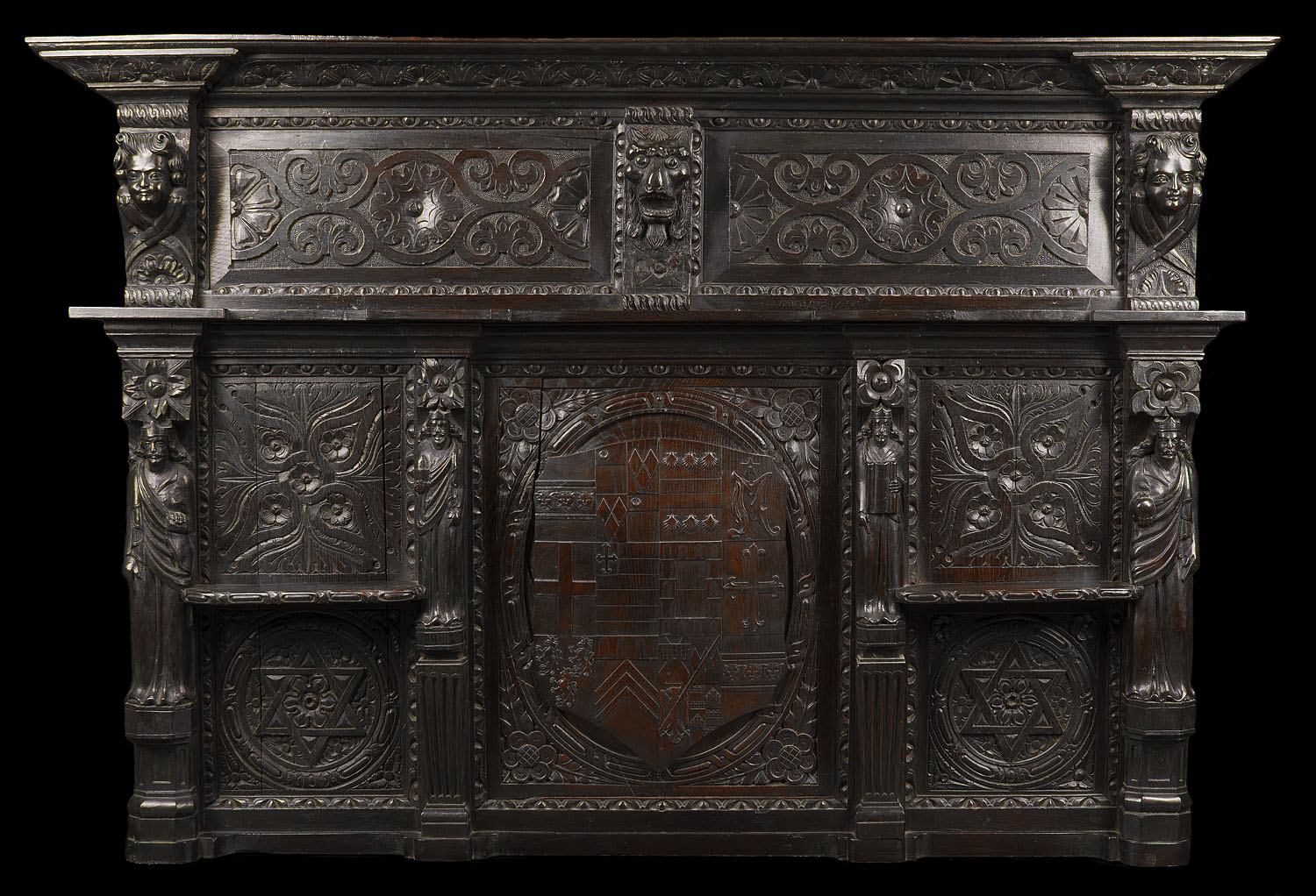 A large antique Jacobean style carved oak overmantel