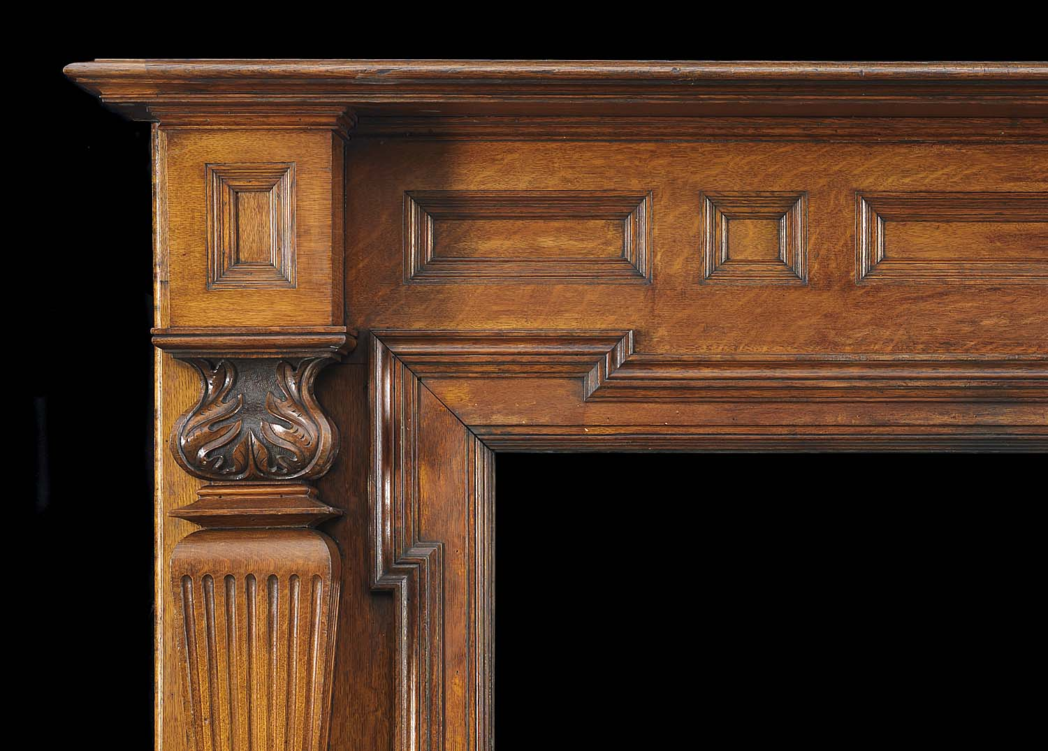 A large antique carved oak fireplace surround in the Palladian style