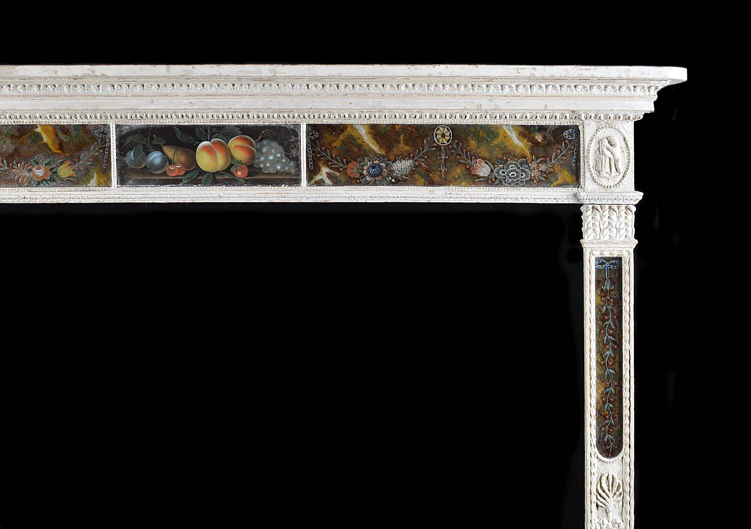 A fine antique Georgian pine and verre eglomisé fireplace surround