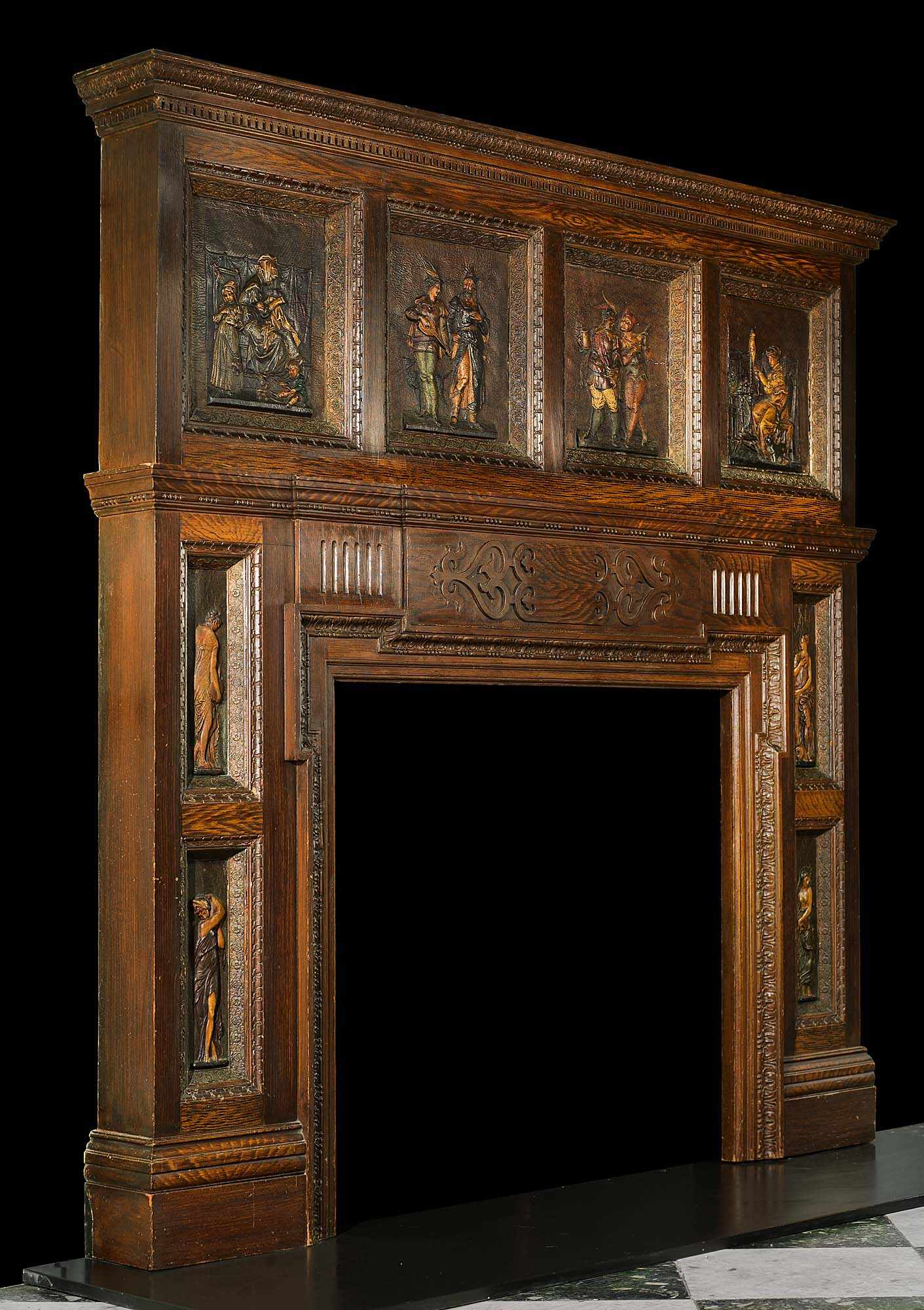 A carved & painted pine illustrative Medieval style chimneypiece. English 1920s.