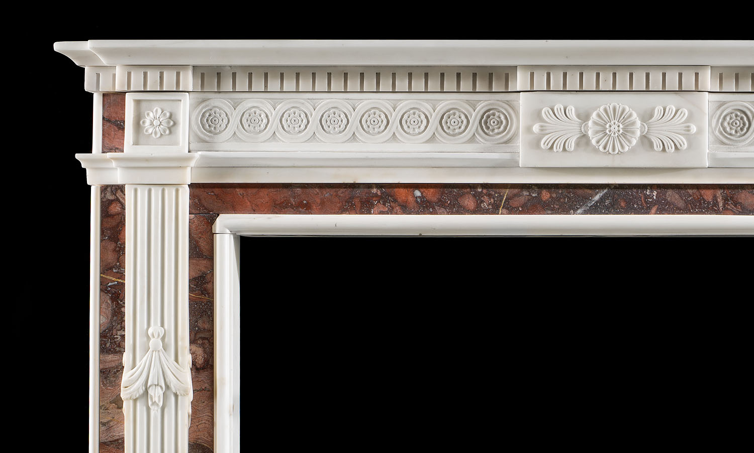 An early 20th century Neopcalssical style fireplace surround.