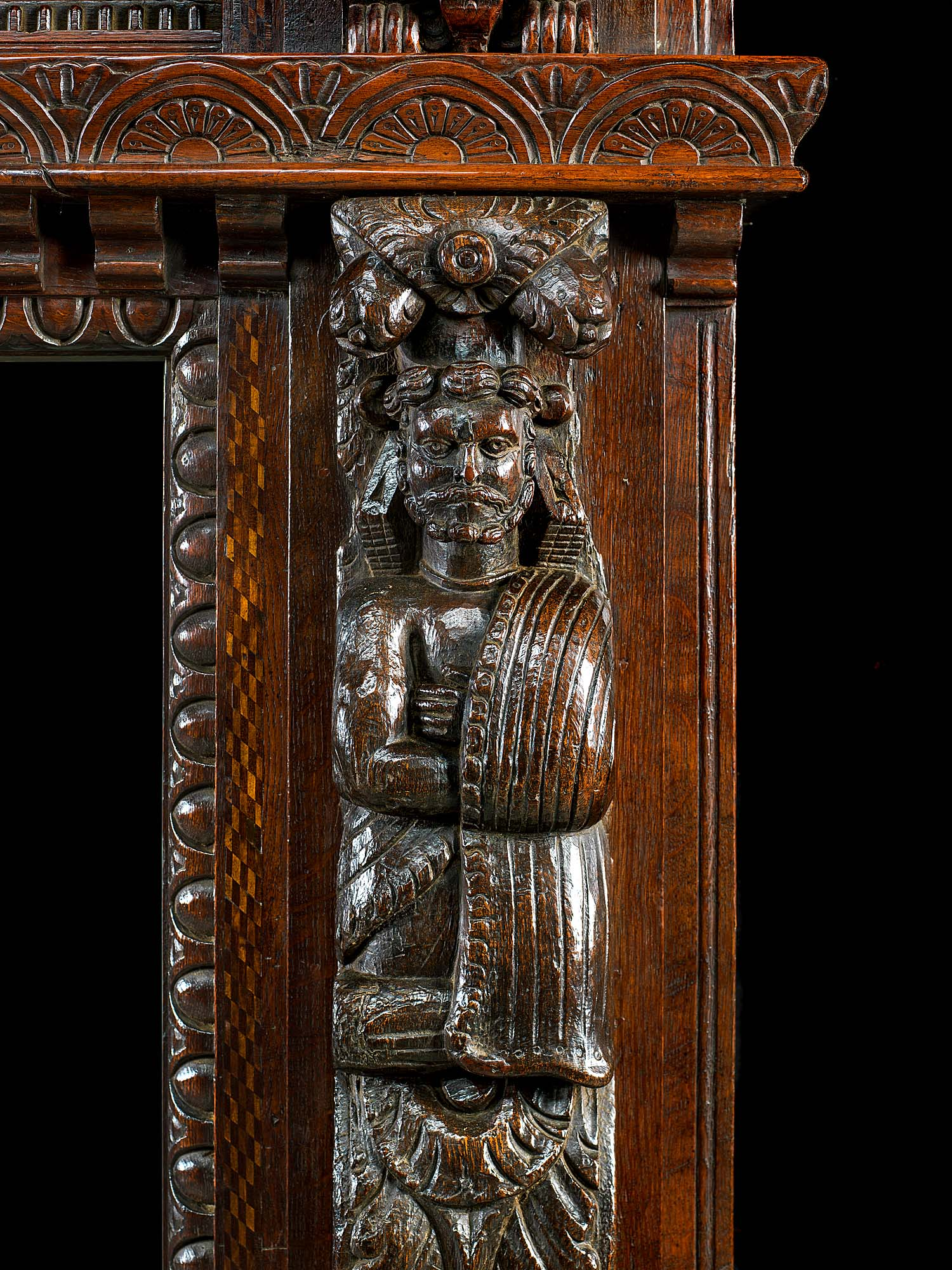 A substantial deeply carved oak Jacobean style antique fireplace