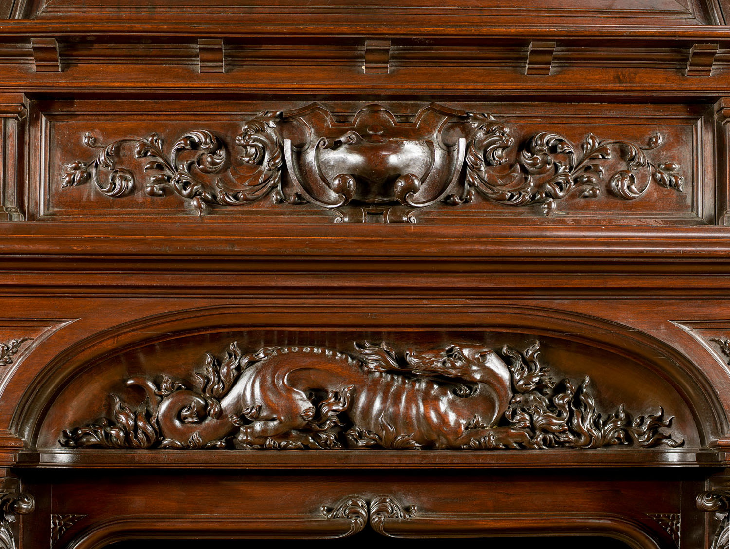 An antique carved walnut Renaissance style Trumeau fireplace