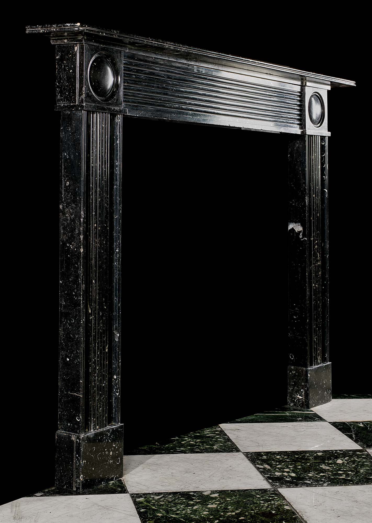 An Antique Regency chimneypiece in black fossil marble