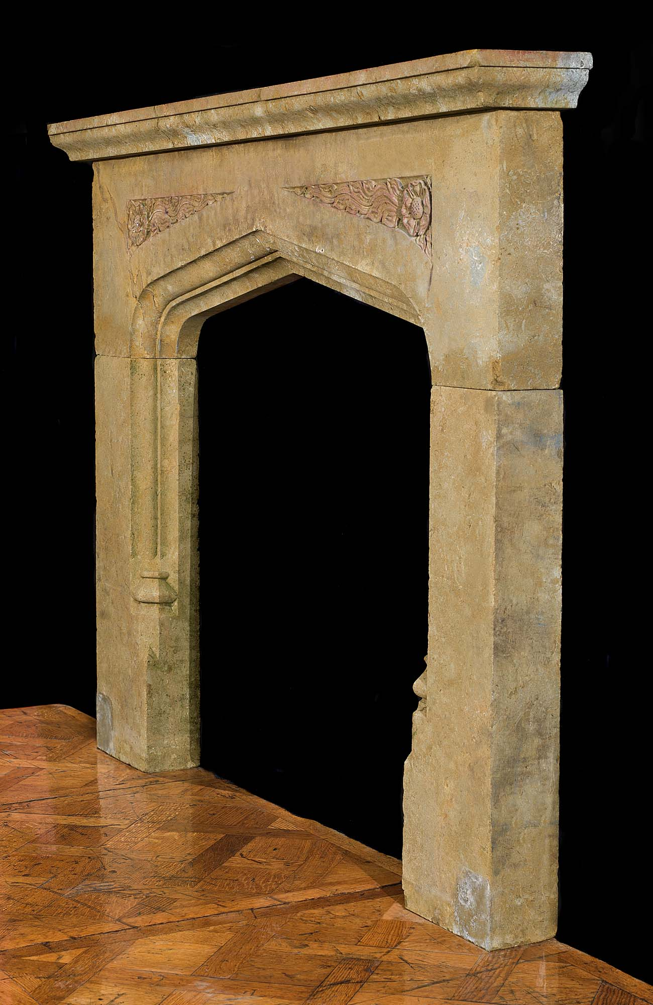 A carved stone 20th century fireplace mantel in the Tudor manner
