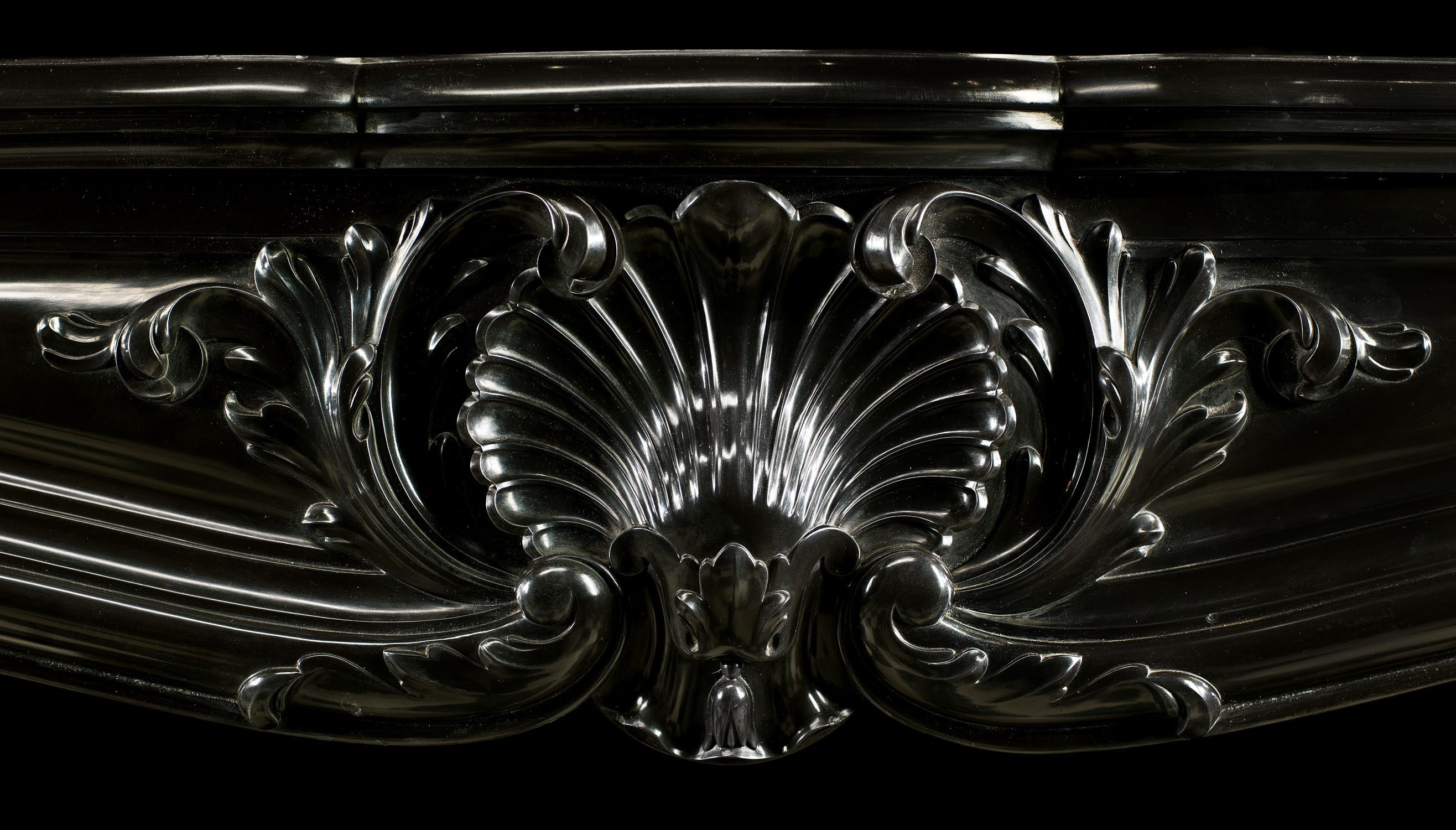 An elegant Belgian Black Marble French Louis XV style Rococo antique chimneypiece.