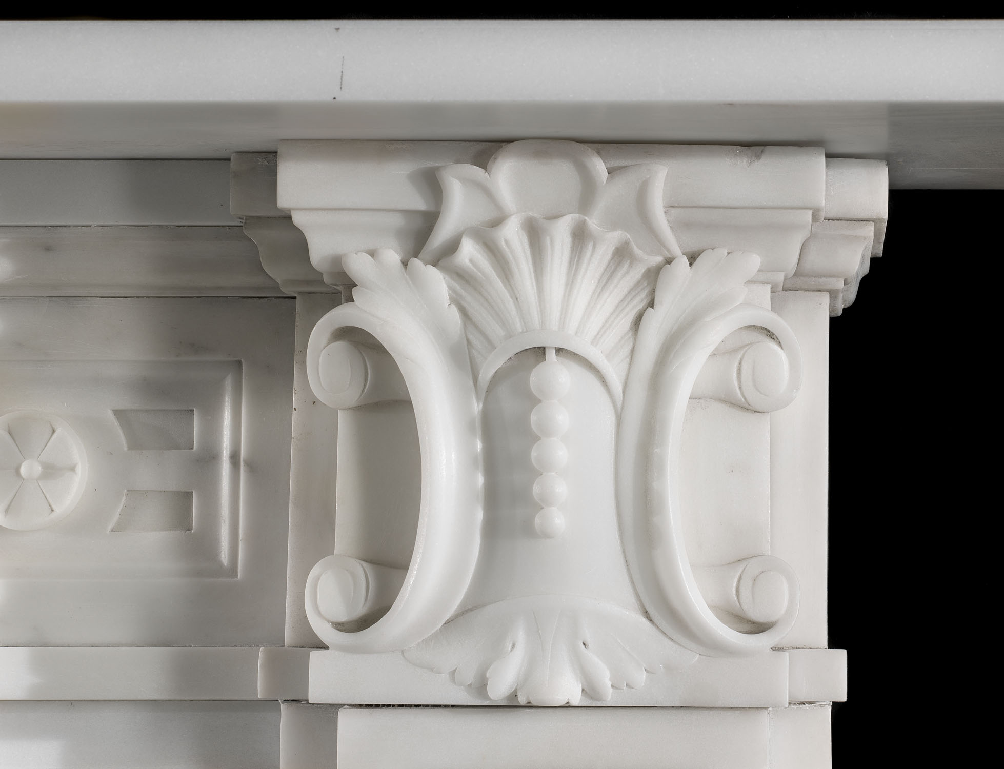 An antique Victorian fireplace mantel in white statuary marble