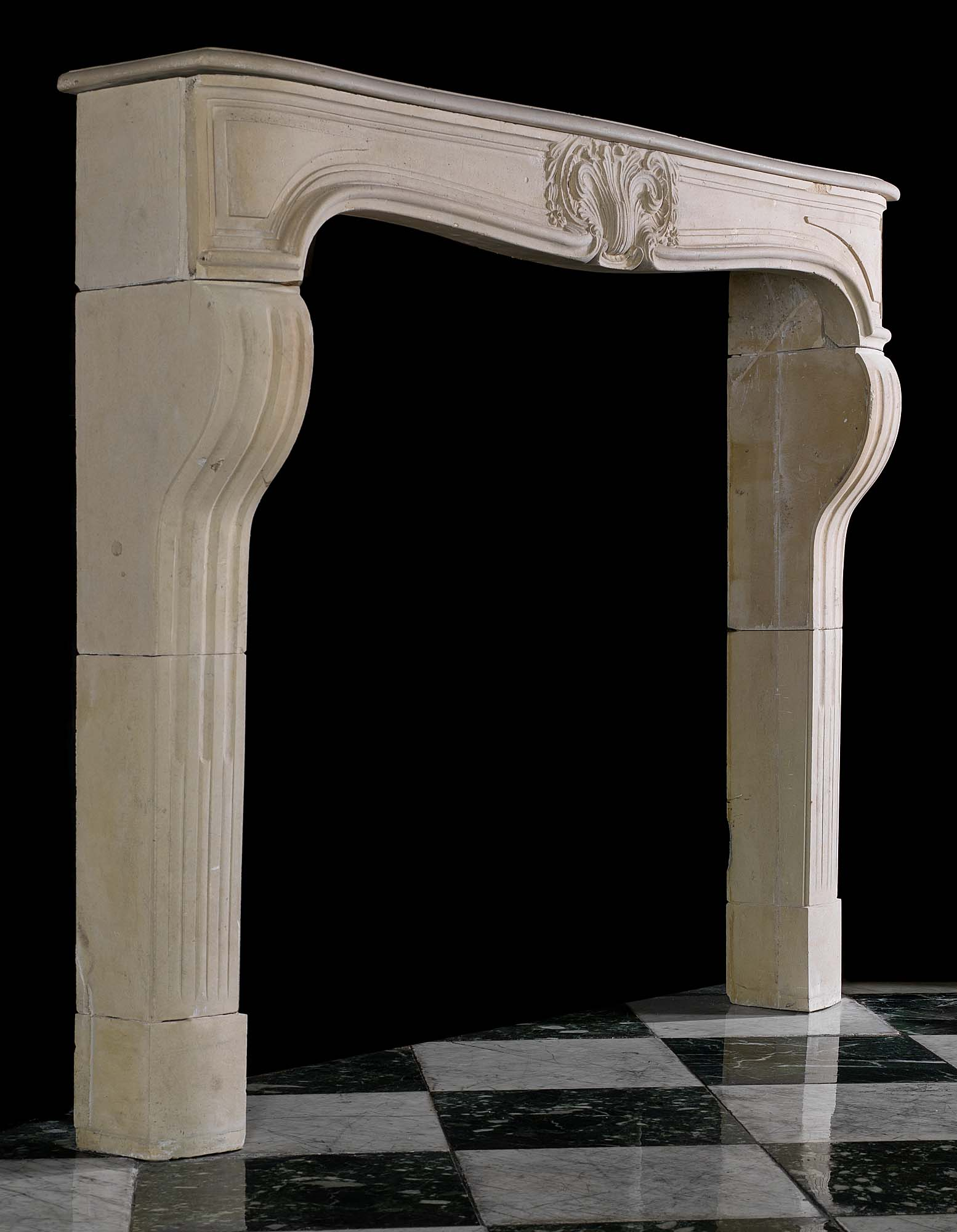 A French Louis XV antique limestone chimneypiece