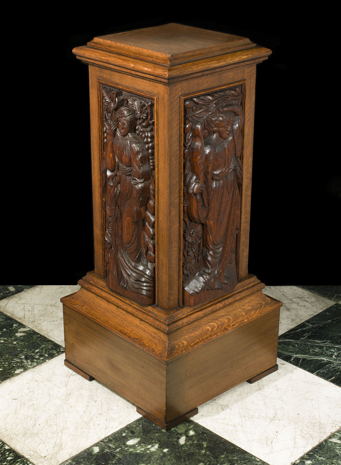 An antique Arts and Crafts carved oak pedestal