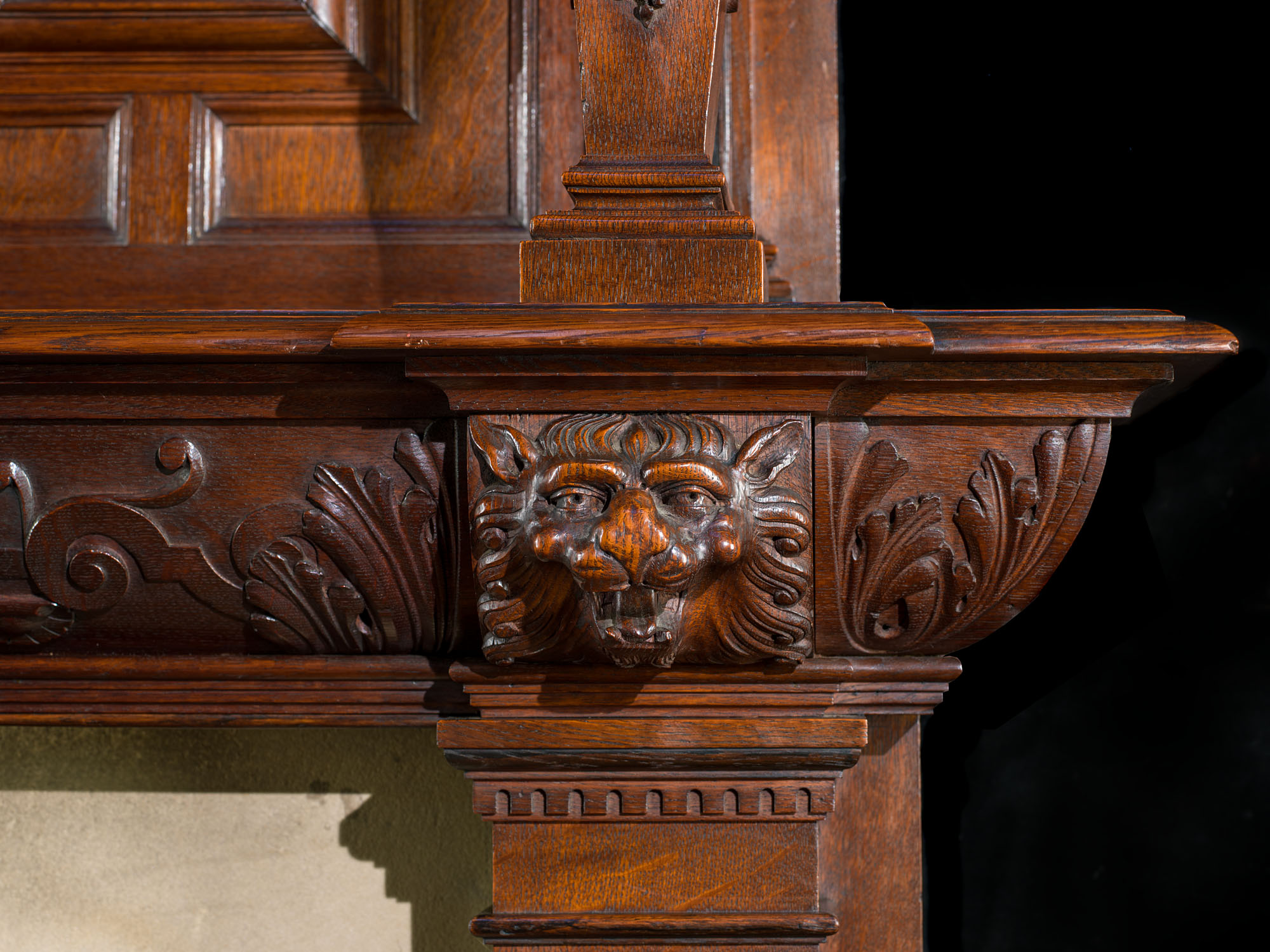 A large antique Jacobean style oak & ebony fireplace and overmantel.