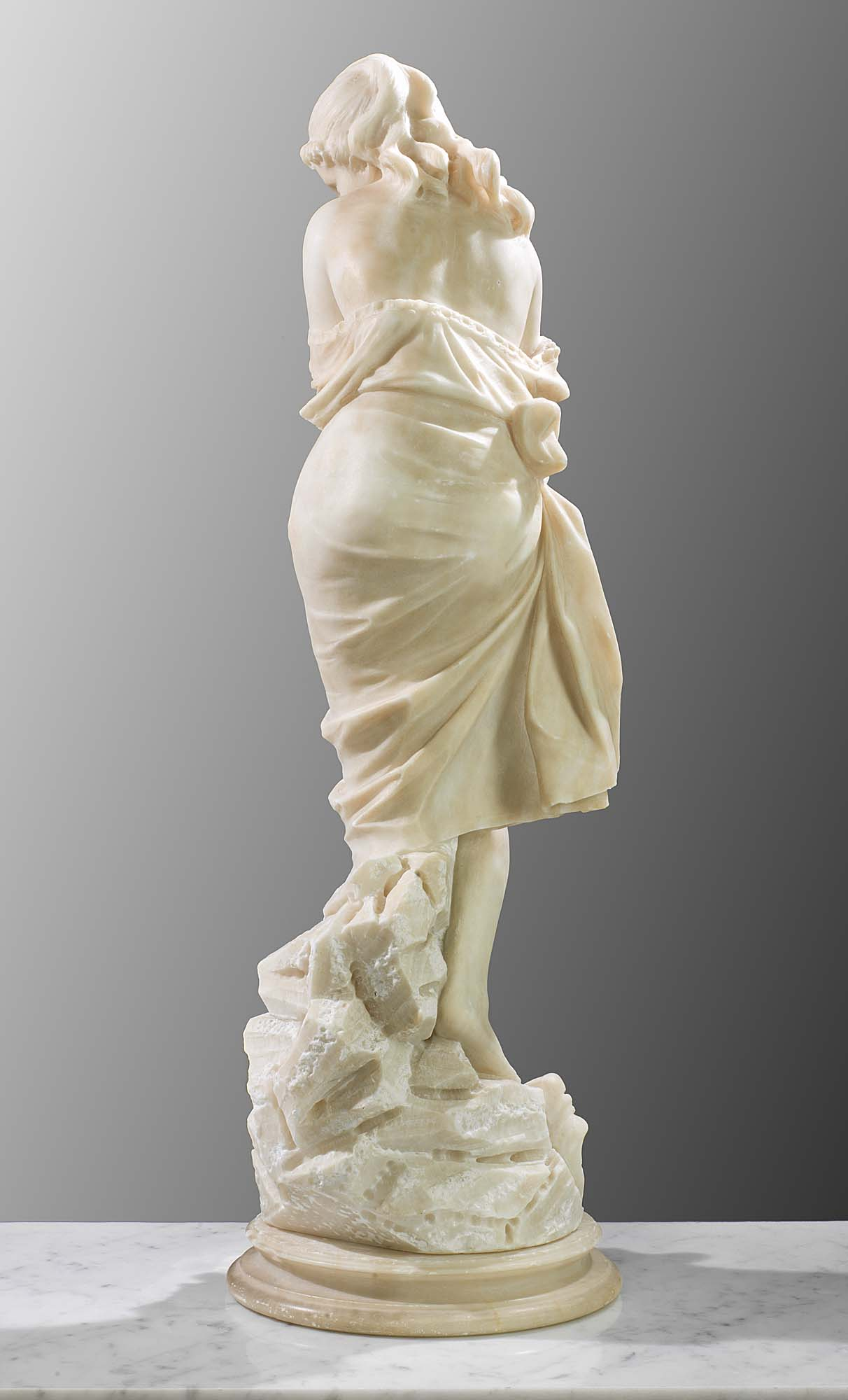 A carved Italian antique Alabaster figure of a young bather.