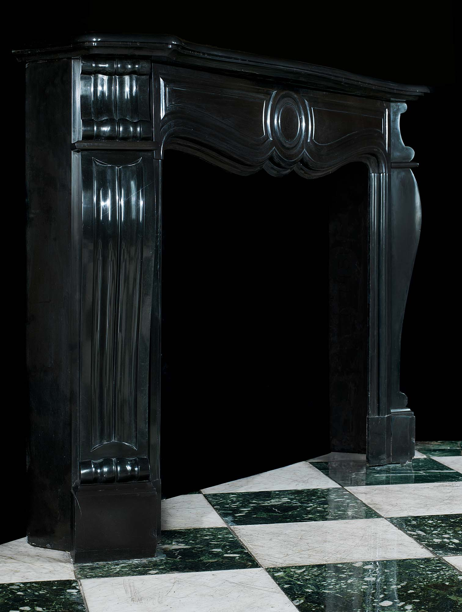 A Belgian Black Marble Rococo style Fireplace Mantel