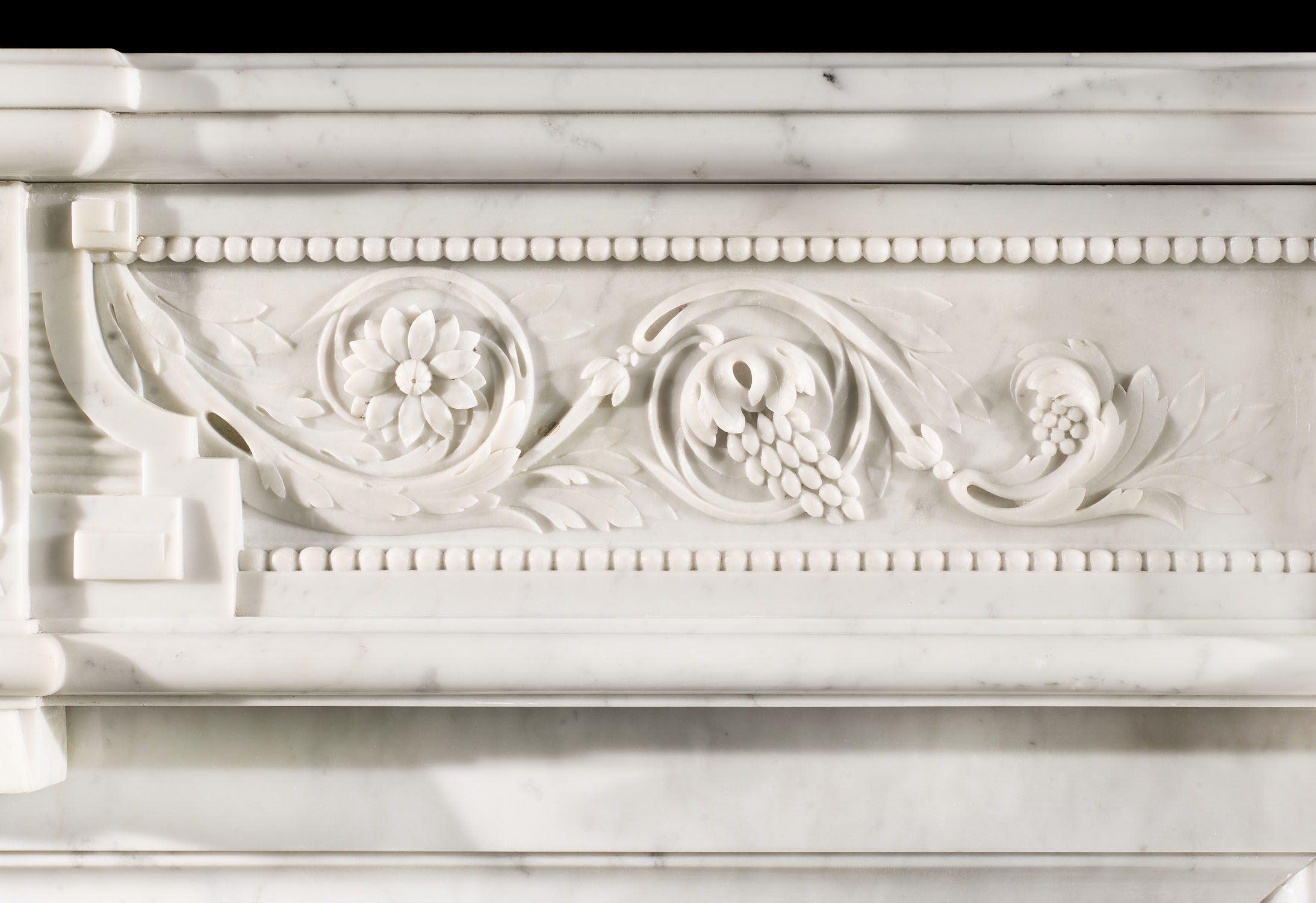 A beautifully carved French Louis XVI style antique fireplace surround