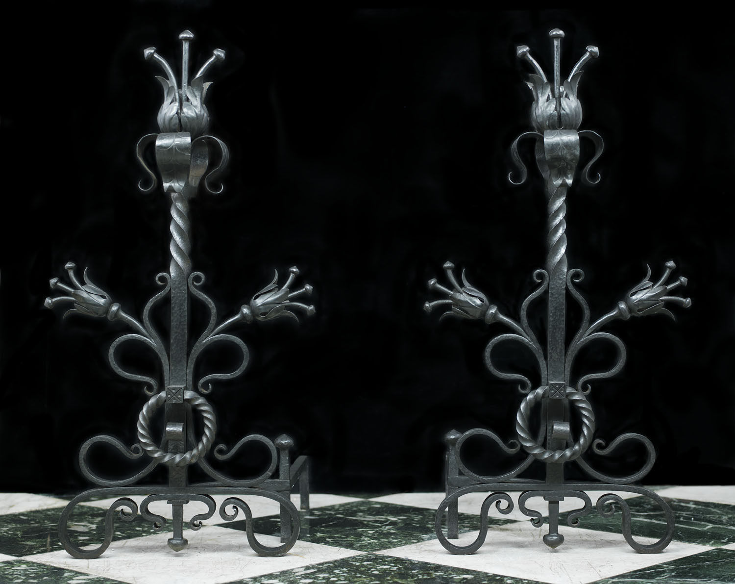 A pair of Arts and Crafts wrought iron fire dogs