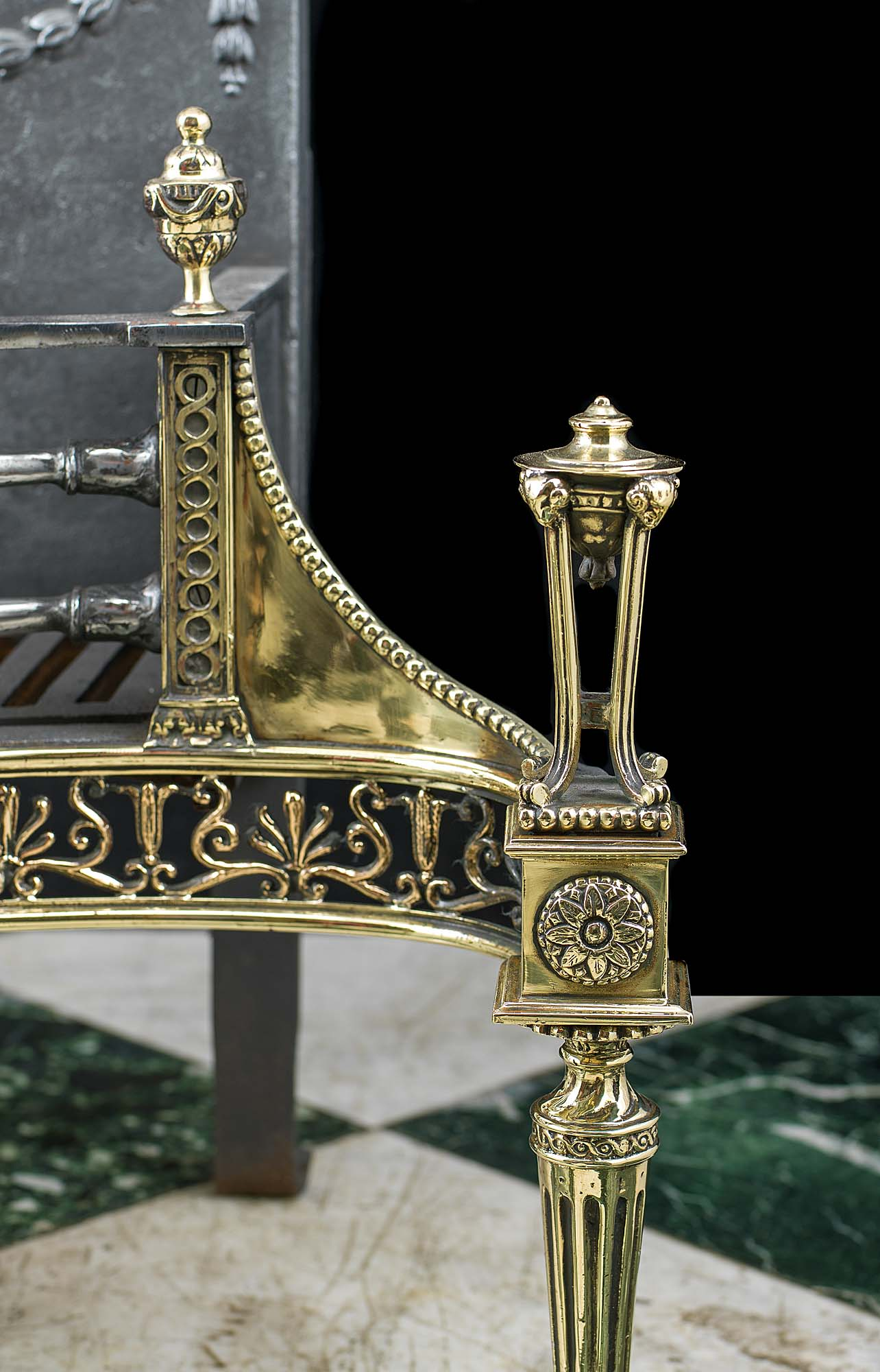 An ornate Regency style cast iron and brass antique fire grate