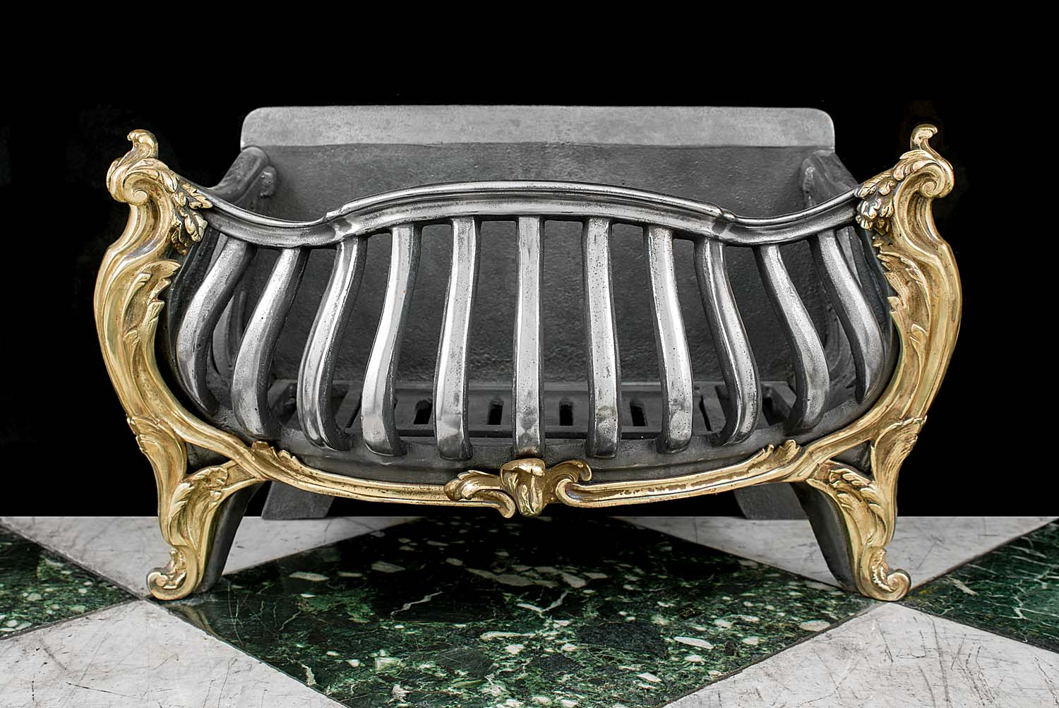 A shapely Rococo style iron and brass antique fire basket