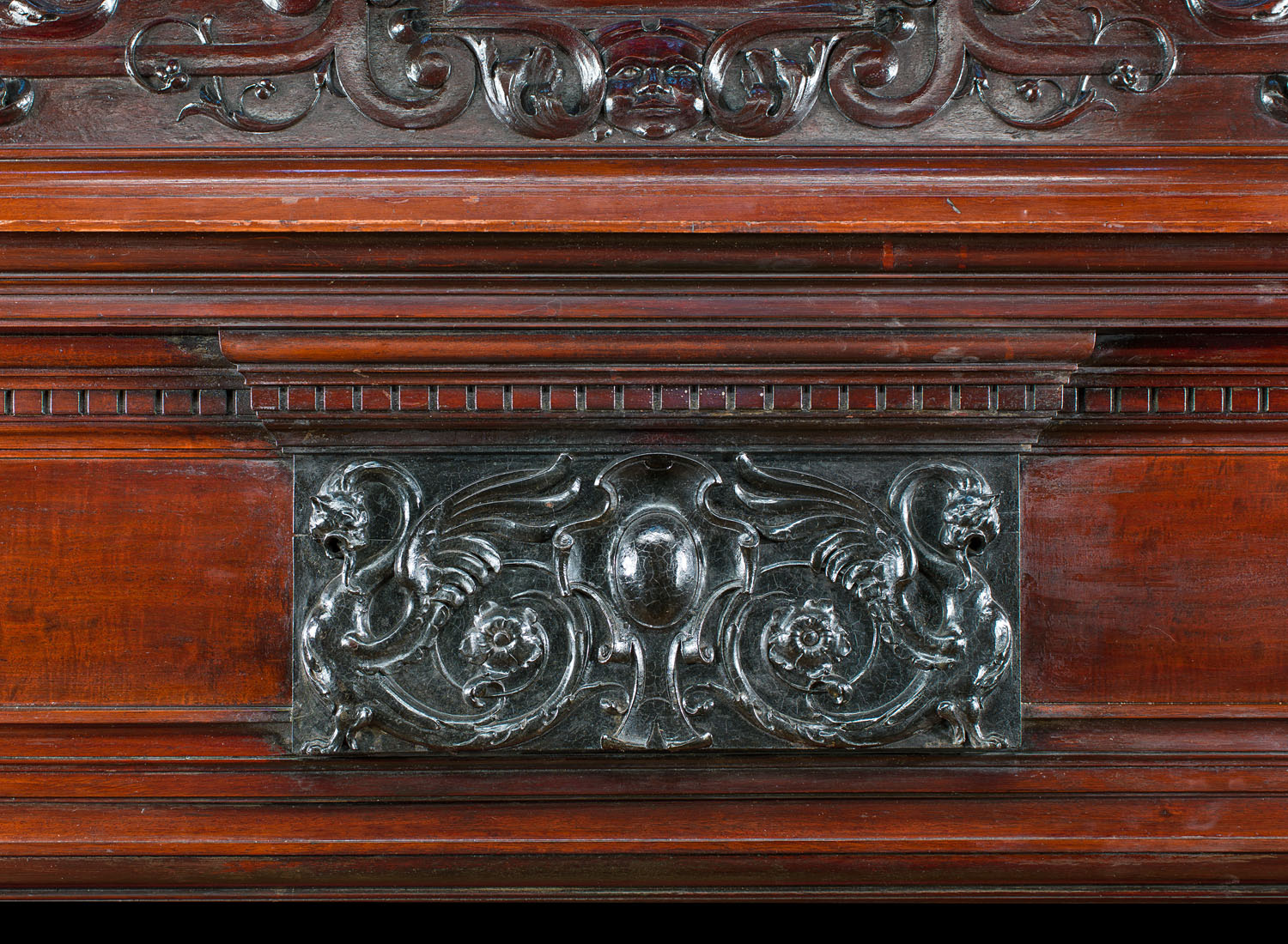 A Baroque style mahogany fireplace and overmantel.