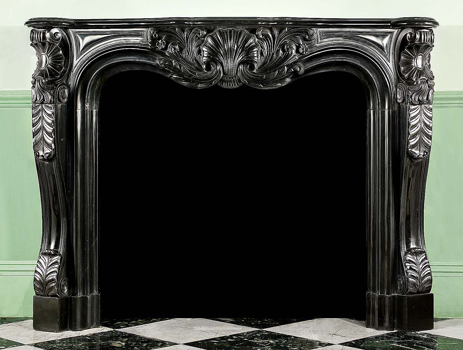 One of a near pair of Antique Louis XV chimneypieces carved in namur black marble