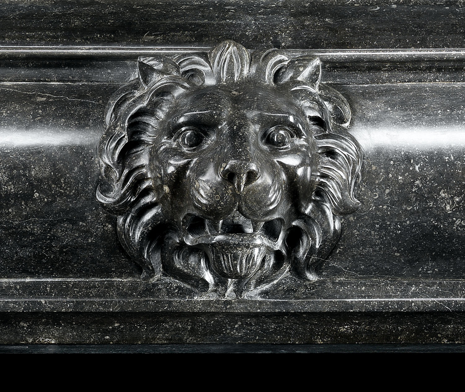 Antique Flemish dark fossil stone baroque Mannerist fireplace mantle This grand Flemish Baroque chimneypiece has double contra scrolling tapering jambs which culminate in lion paws. These support a barrelled integral shelf and frieze which is centered by a magnificent lion's mask. 16th century and later.