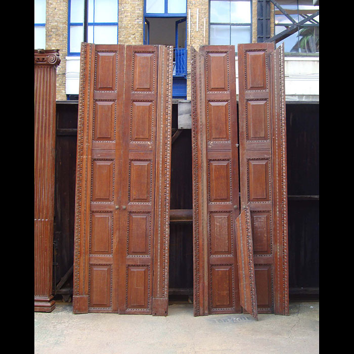 10027: Two pairs of 5 panel carved oak doors, raised and fielded panels with egg and dart carved borders together with floral carved architrave on 3 sides. Early 20th century.Ensuite with 10025 a large pair