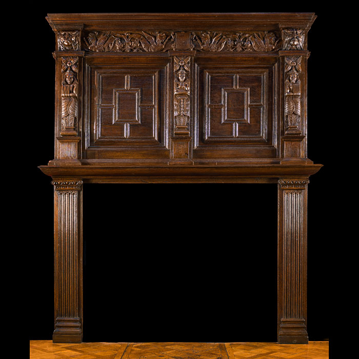 10564: A tall antique carved oak fireplace surround & overmantel. The surround with fluted corinthian column jambs and a cushioned mantel shelf, the overmantel with two quartered panels separated by three pi