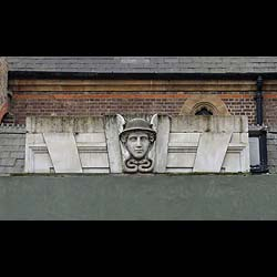 10669: A CARVED PORTLAND STONE OVERDOOR featuring the head of Mercury on the central keystone, English, late 19th century.