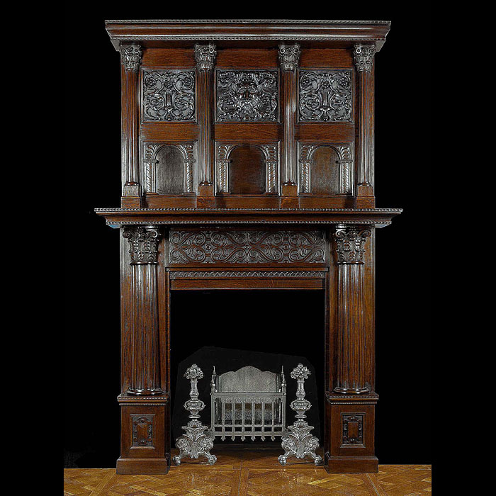 10847: THE GREEN MAN CHIMNEYPIECE:A large well carved oak chimneypiece in the English Jacobean manner.The overmantel with four fluted columns topped by ornate capitals enclosing two rows of three panels, the