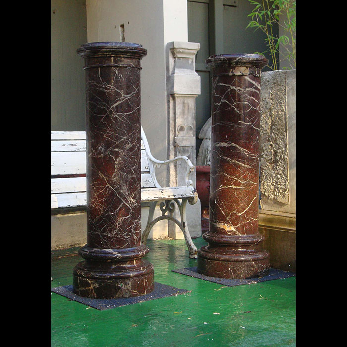 Pair of red marble columns with revolving tops