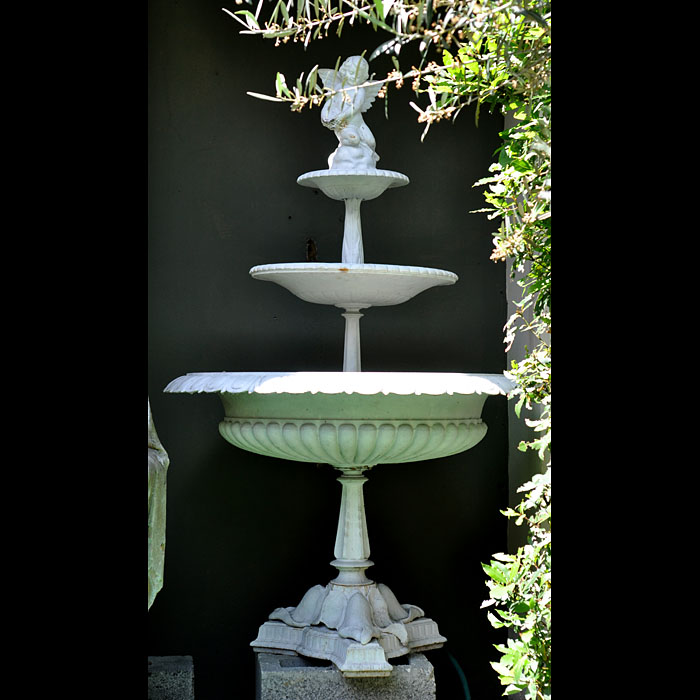 11334: A slender classical three tiered painted cast iron fountain surmounted by a winged cherub and with the foundry mark of the Handyside Foundry, Glasgow on the base stem. Late 19th century.