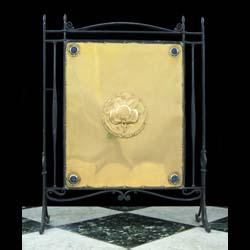 11427: A fine delicate and Arts & Crafts wrought iron and brass fire screen. The large brass rectangular panel embossed with a central floral roundel & four corner, blue-glazed, circular pottery cabochons.En