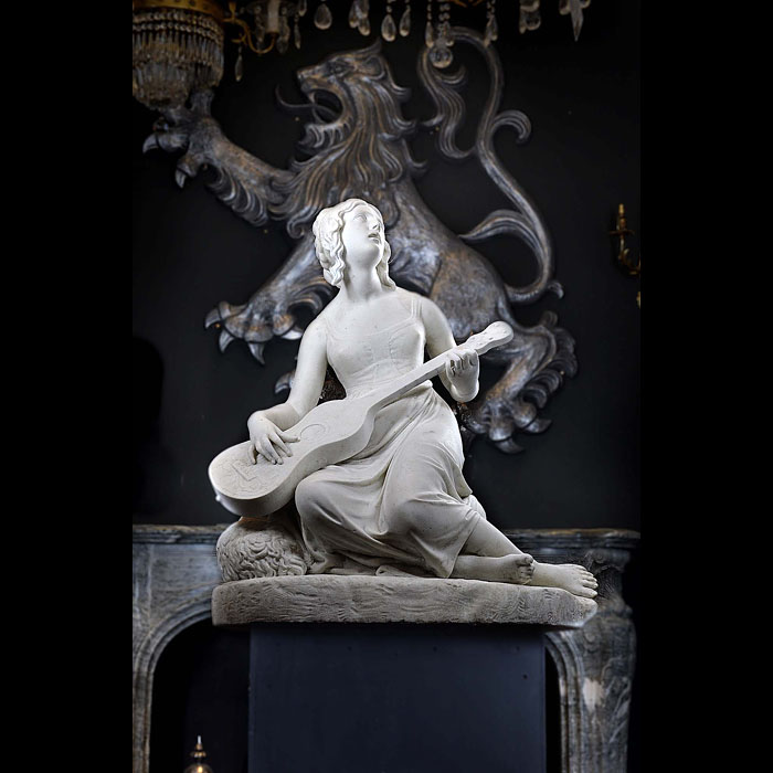 11480: A well carved white Statuary marble maiden musician seated on a rock dressed in simple 18th century garb playing a guitar with her attentive, adoring tousle-haired dog lying beside her. French / Itali