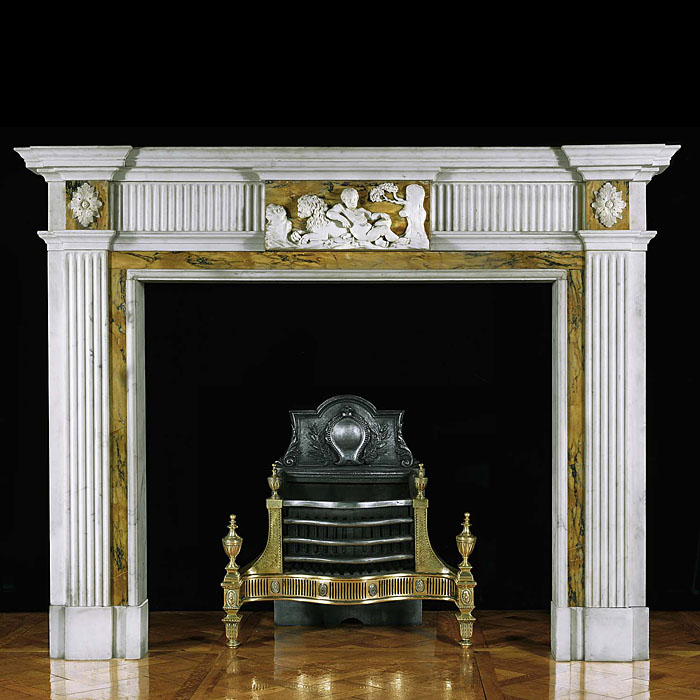 11666: A well proportioned George III chimneypiece in white statuary marble with Sienna marble inlay.The breakfronted shelf is supported on the freize with fluted side panels flanking a central tablet in Sie