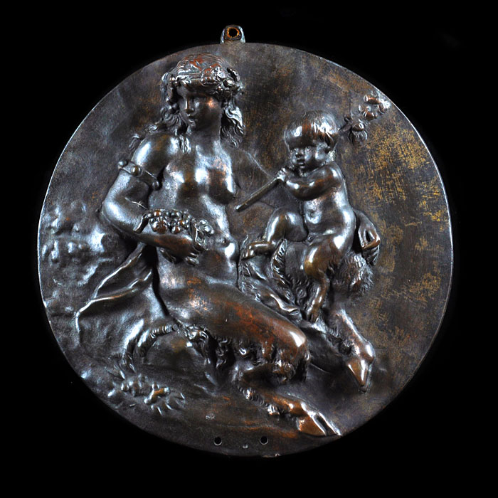 An antique bronze roundel of a faun and putti