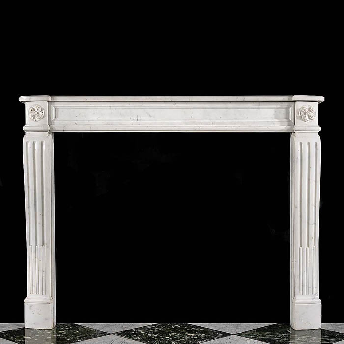 11773: An elegant, small Louise XVI faintly veined statuary marble chimneypiece with a simple panelled frieze flanked by a pair of floral roundels on the endblocks set above reeded, stop fluted jambs.French