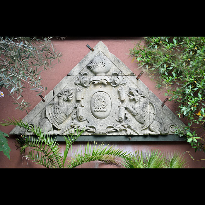 11910: A LARGE TRIANGULAR CARVED BATHSTONE ARMORIAL PEDIMENT depicting a Coat of Arms of a Knights helmet surmounting a central floral Cartouche with a Lions head profiled set within an ova Lozenge, the the