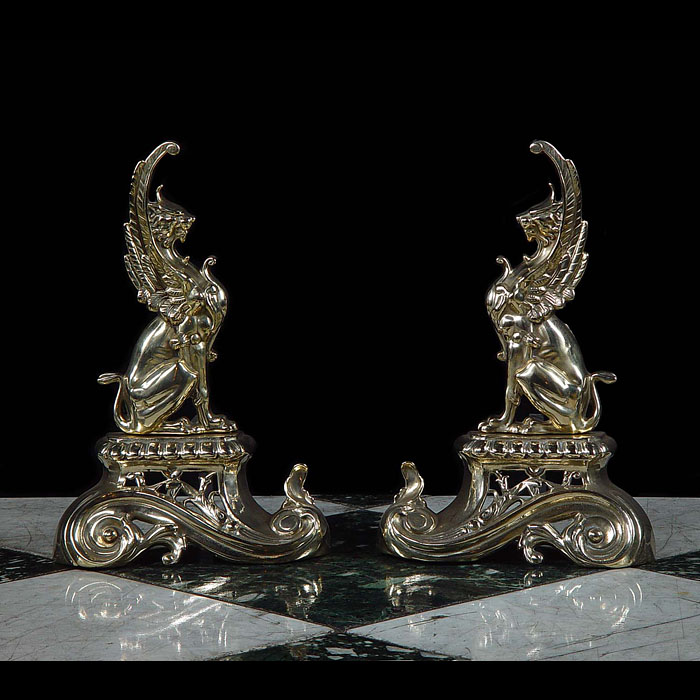 A pair of antique brass Rococo style griffin fire dogs