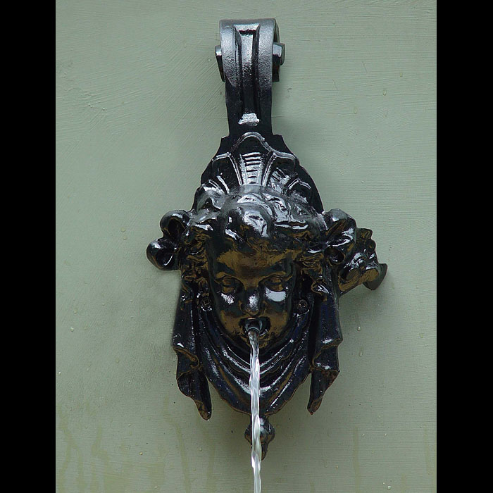 11961: A small cast iron wall fountain spout in the Baroque manner in the form of a putto's head.English,19th Century.   Link to: Antique fountains, sculptures, garden furniture and statuary