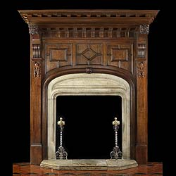 12050: A large Jacobean Revival carved oak fireplace and overmantle with shaped Portland Stone ingrounds, hearth & fender. There are two carved lions masks over the brackets supporting the canopy flanking th
