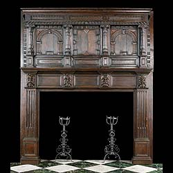 12121: A Large Jacocbean Period Carved Oak Chimneypiece & Overmantel with its original dark patinated finish.The overmantel with cluster columns and arched panels above the deep panelled fireplace frieze set