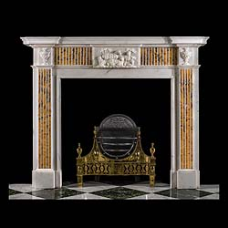 12125: A George III style chimneypiece in white statuary marble with inlaid Sienna marble decoration. The breakfront shelf over the frieze centered by a carved marble plaque of recumbent sheep, flanked by in