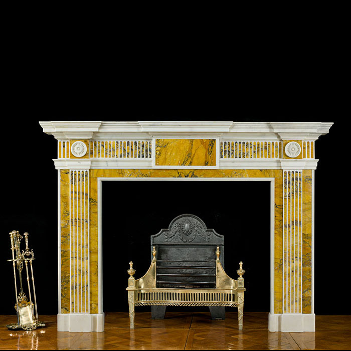 12127: A late Georgian neoclassical fireplace surround in the manner of Robert Adam carved in white Statuary marble with yellow Sienna marble inlay. The wide breakfront shelf set over the fluted frieze centr