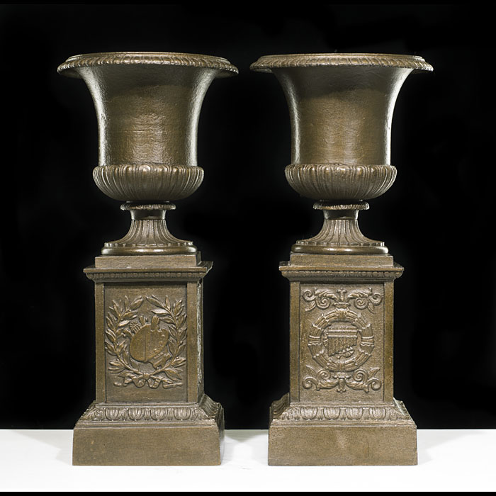 A Small Pair of Cast Iron Urns & Plinths