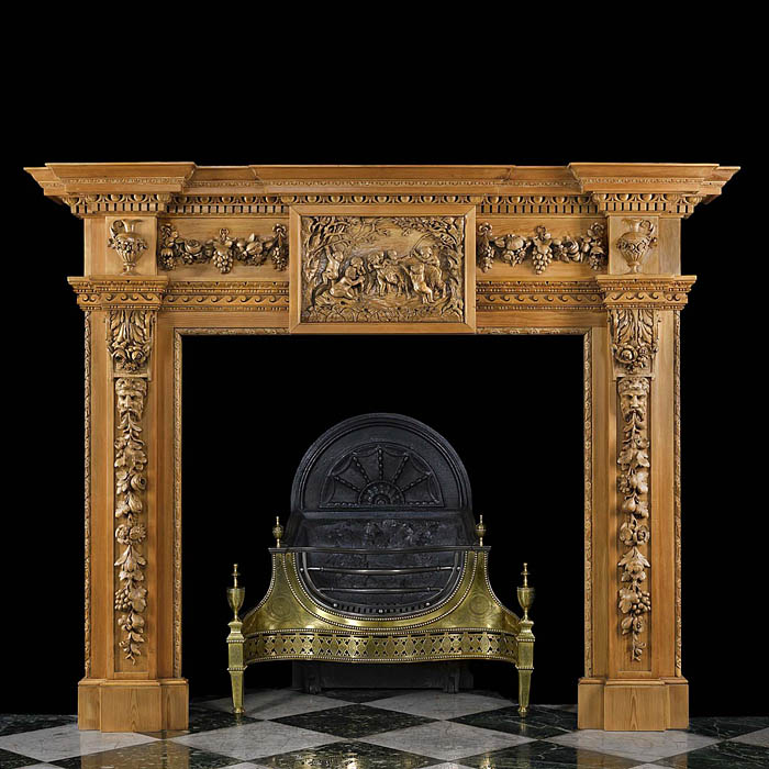 12280: A large pine and limewood chimneypiece in the mid 18th century Palladian manner. The breakfront shelf above a richly carved frieze, centred by a plaque depicting a crowd of putti wrestling with a goat