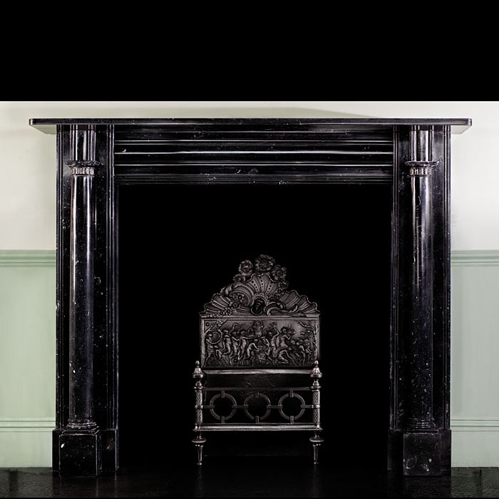 12290: A smart columned Irish Regency Chimneypiece in Kilkenny Fossil Black Marble elegantly carved with tapering columns beneath fluted capitals supporting the deep and lightly fossil strewn shelf. Early 19