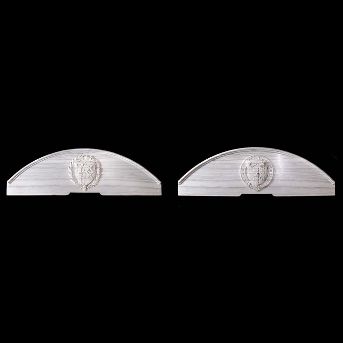 12418: A PAIR OF ARCHED OVERDOORS IN GREEN VEINED WHITE MARBLE, each with a central coat of arms carved in high relief. English late 19th century.