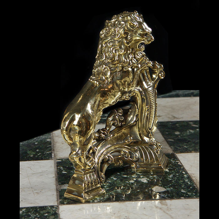 Antique Pair of Louis XIV Lion Chenets in Brass with a decorative armorial shield
